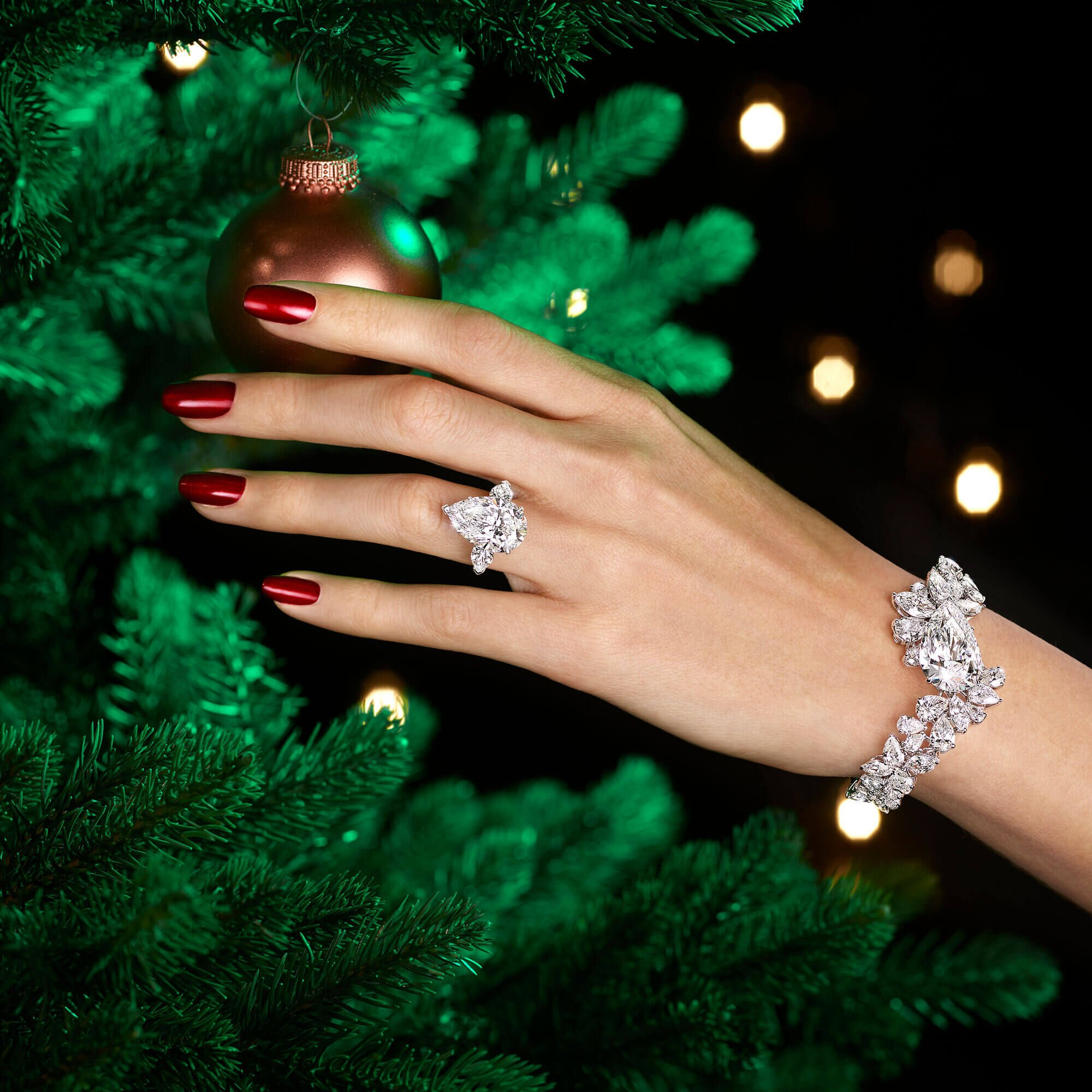 a Graff pear shape diamond ring and diamond bracelet on a lady's hand reaching out to an ornament on a christmas tree.
