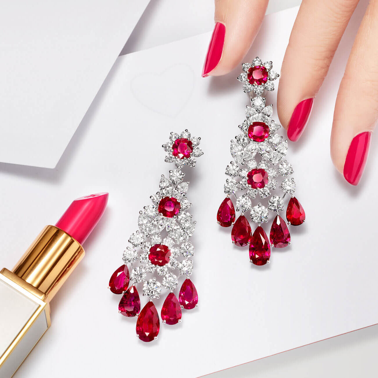 A Graff Ruby and diamond earrings with lipsticks and a lady's hand
