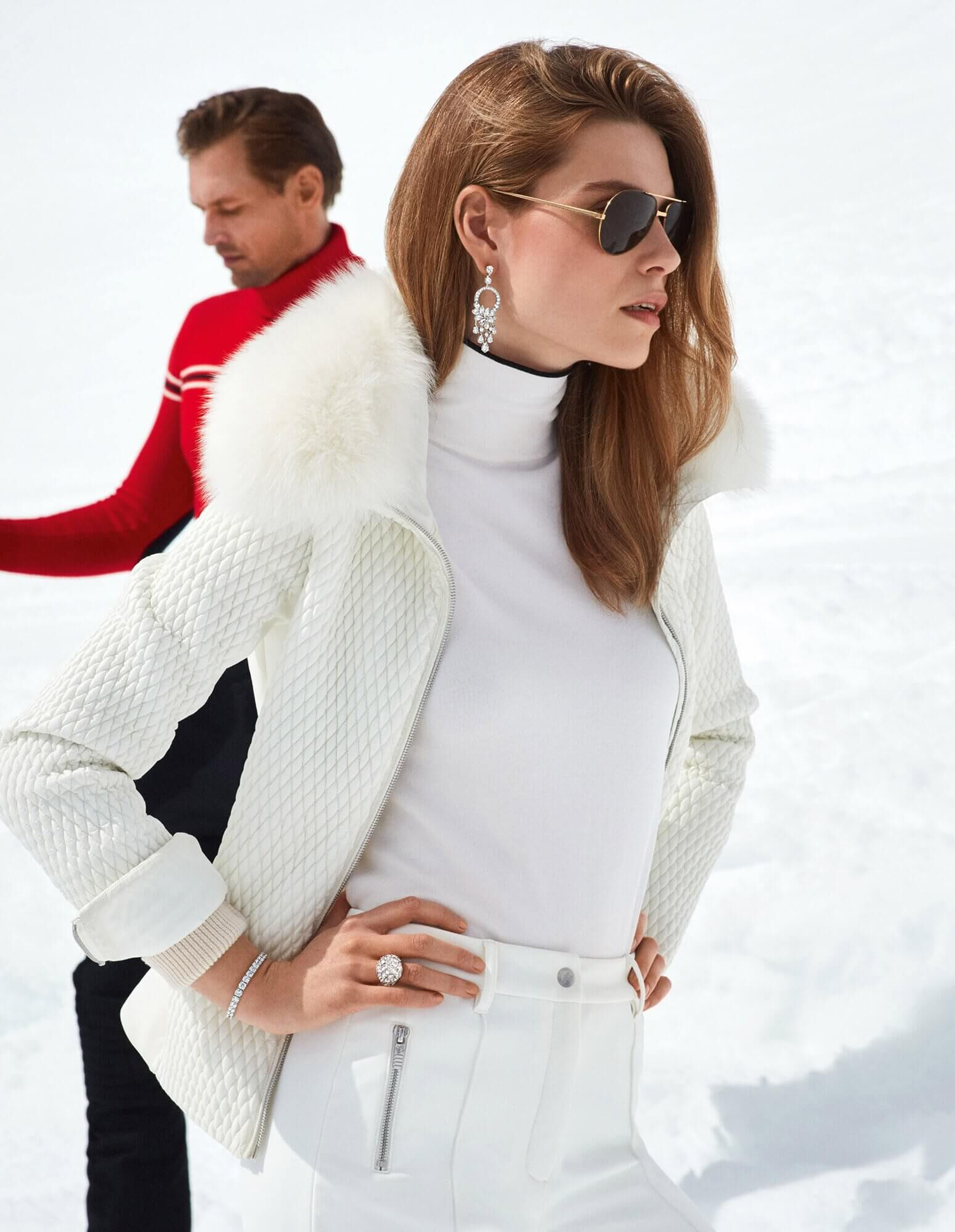 A woman dressed in white on a ski slope wearing abstract diamond butterfly earrings with a round diamond bracelet and a diamond bombé ring