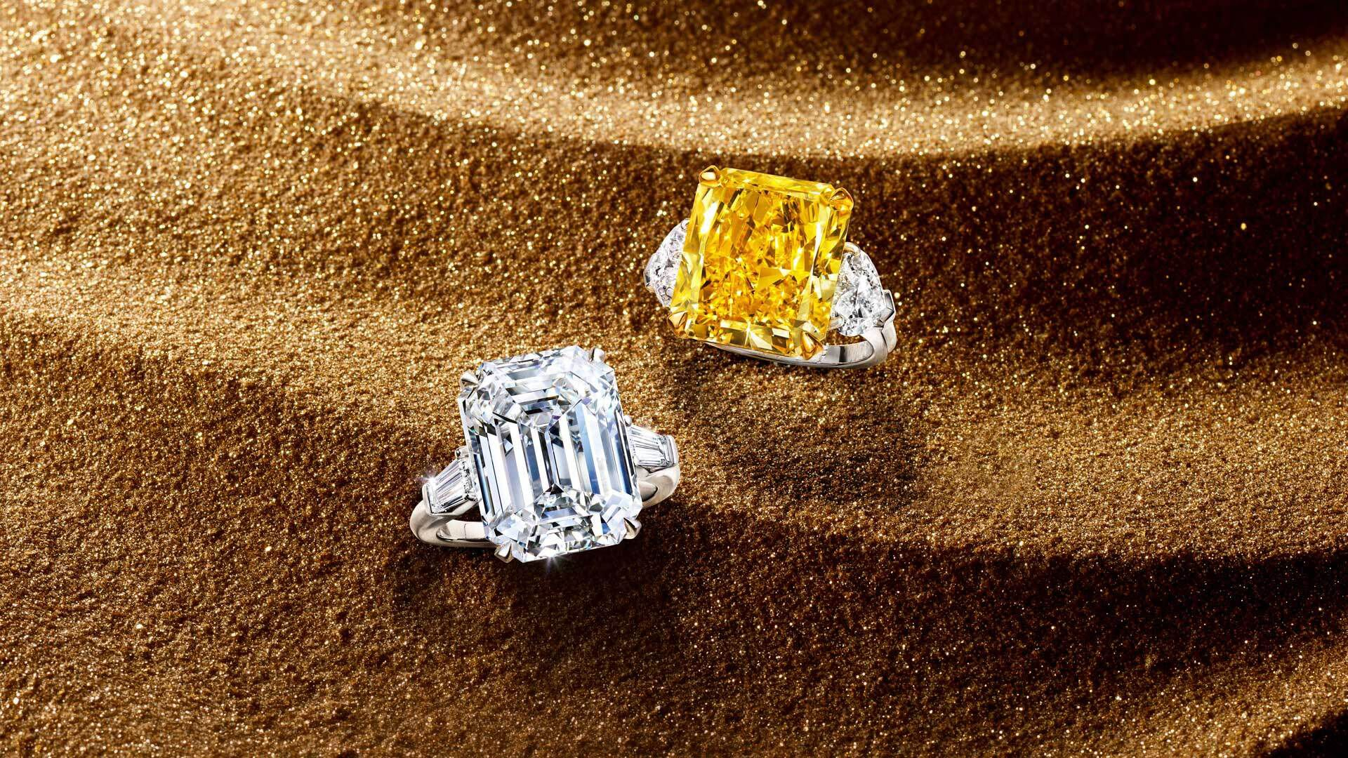 Two Graff Unique Solitaire diamond rings on a sandy background