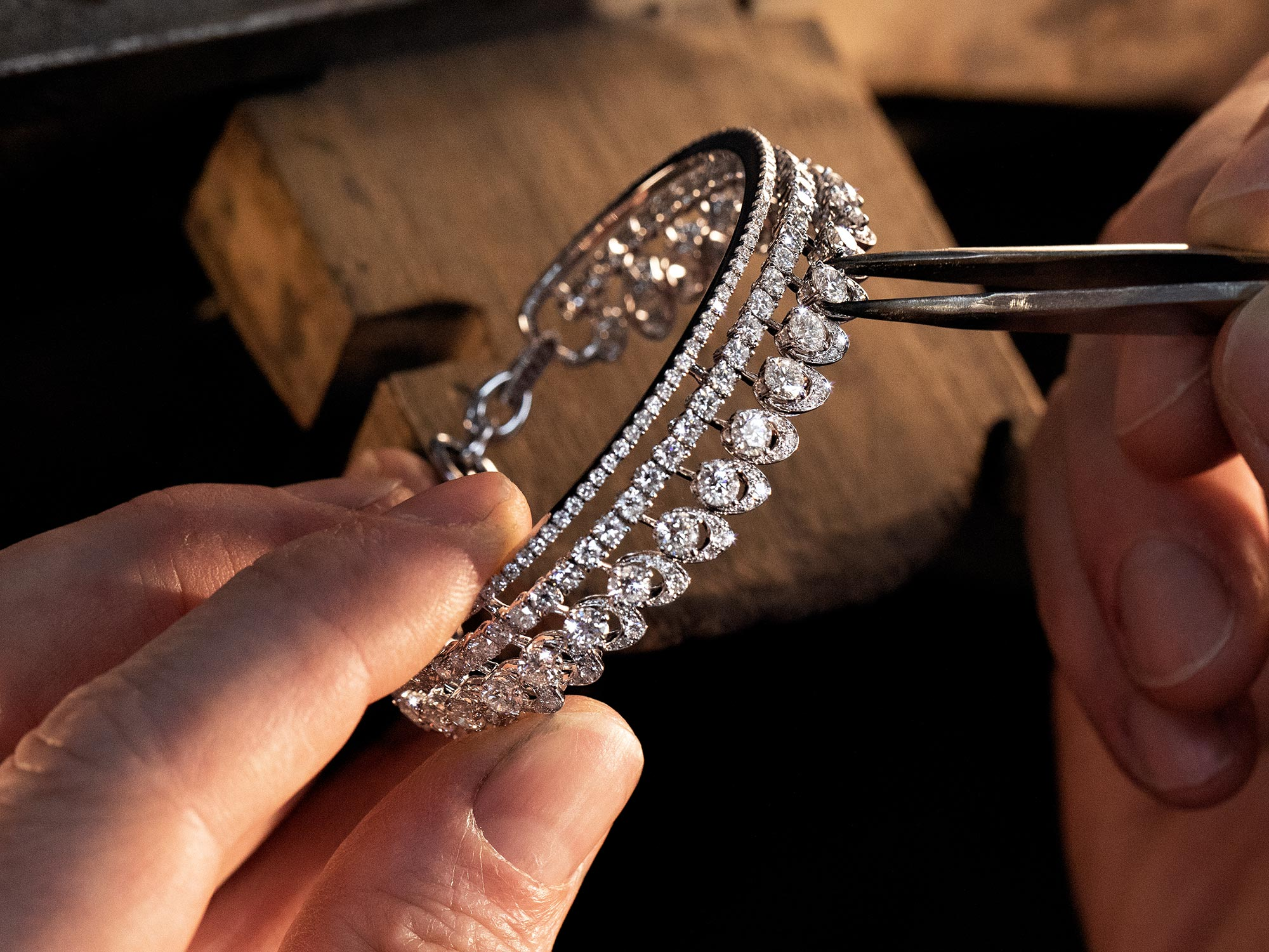 Close up of a Graff craftsman setting the diamonds of the a Gateway diamond bracelet from the Tribal jewellery collection in the workshop