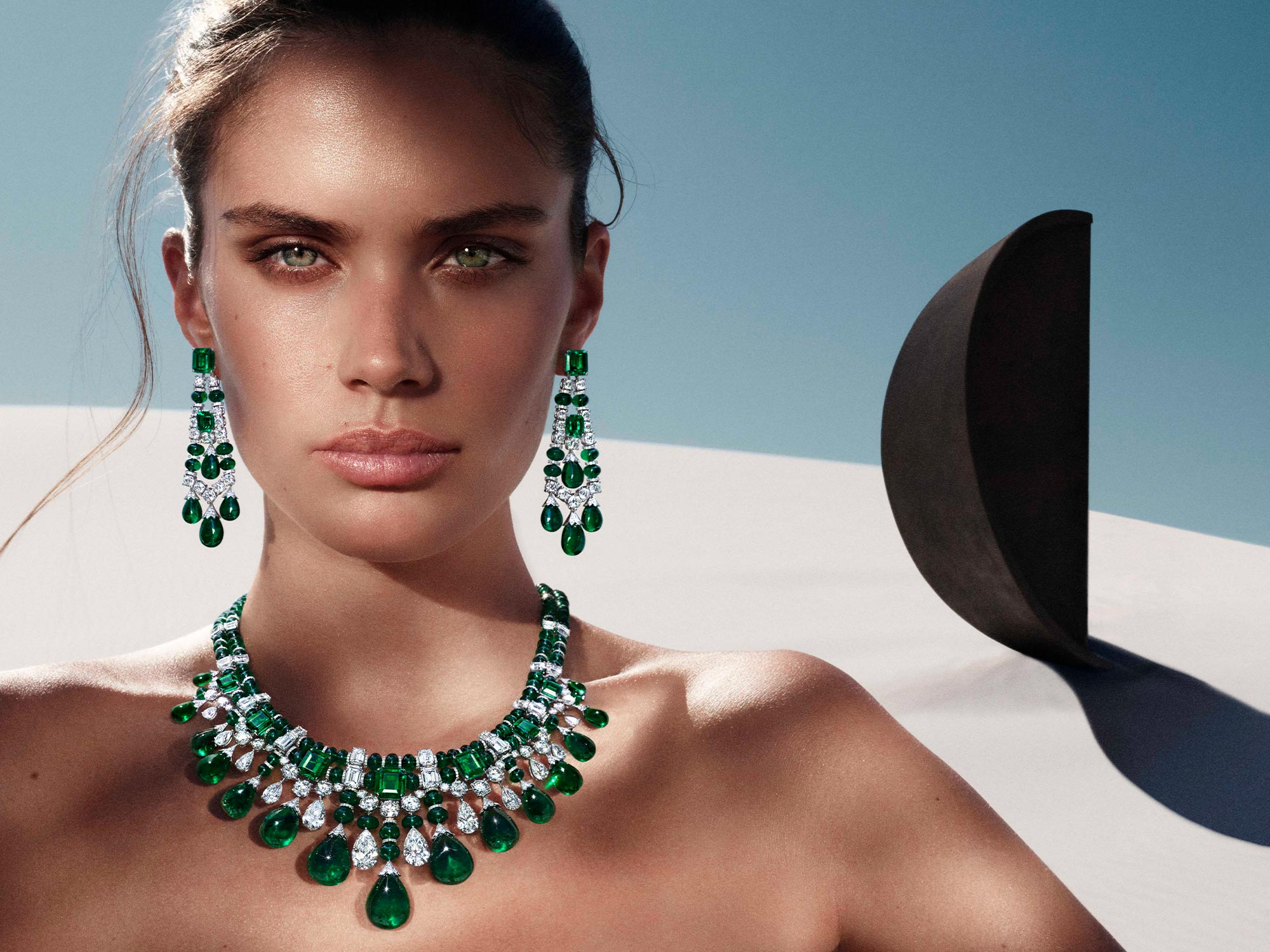 Close up of a model wearing Graff Night Moon emerald and diamond high jewellery earrings and necklace from the Tribal jewellery collection, in a desert in front of a black sculpture