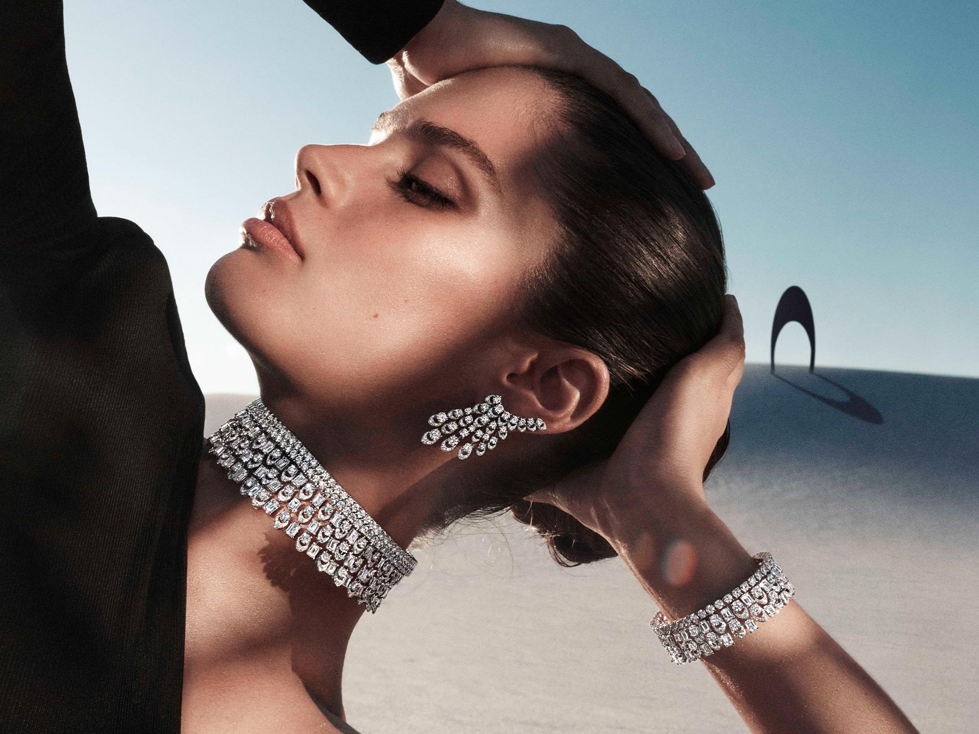 Close up of a model wearing Graff Gateway diamond earrings, necklace and bracelet from the Tribal jewellery collection, in a desert