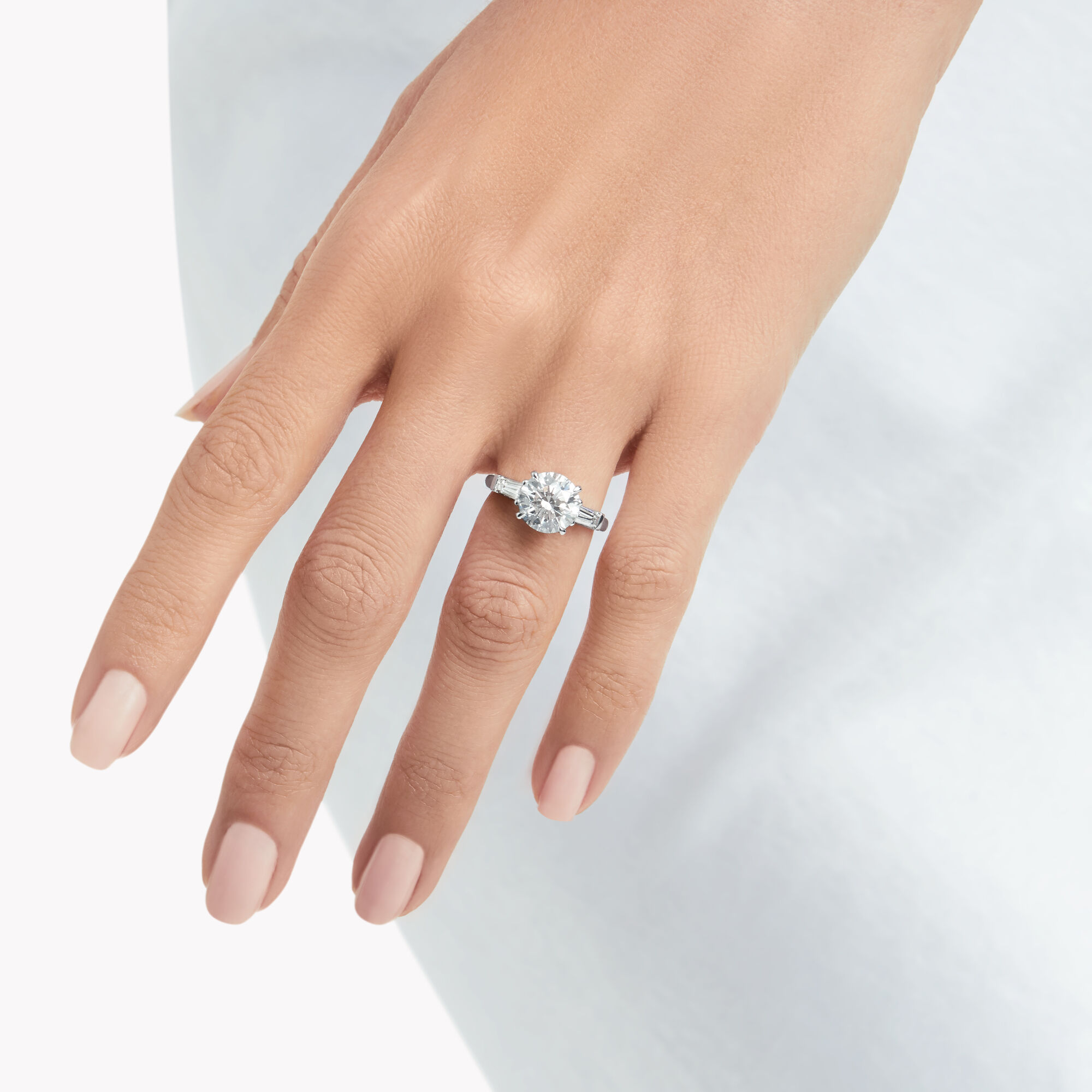Model wears Promise Round Diamond Engagement Ring with baguette side stones from the Graff Bridal collection