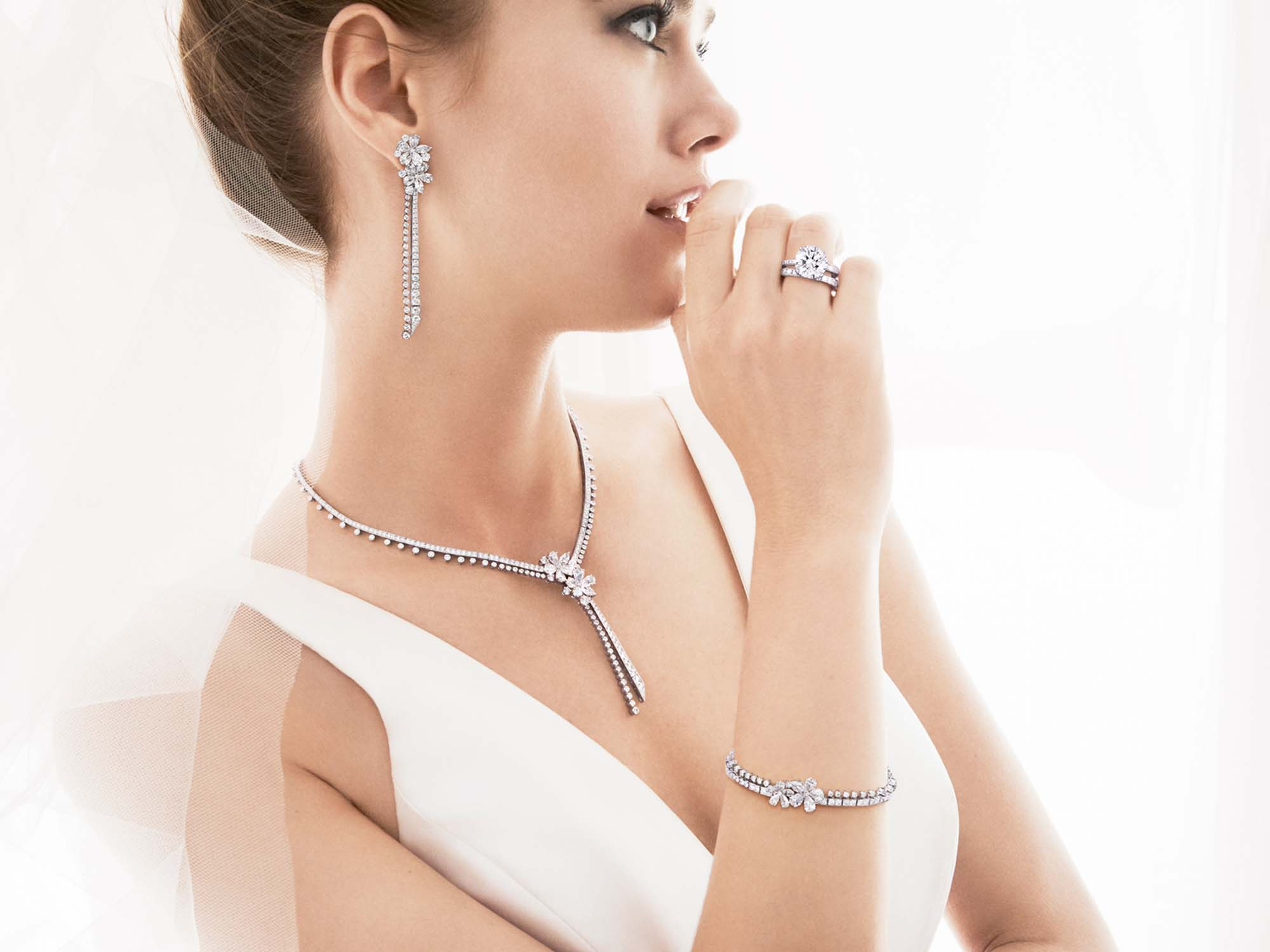 Model wears Graff Carissa Diamond Drop Earrings, Carissa Diamond Drop Necklace, Carissa Diamond Bracelet, Round Diamond Solitaire and Castle Set Round Diamond Wedding Band.