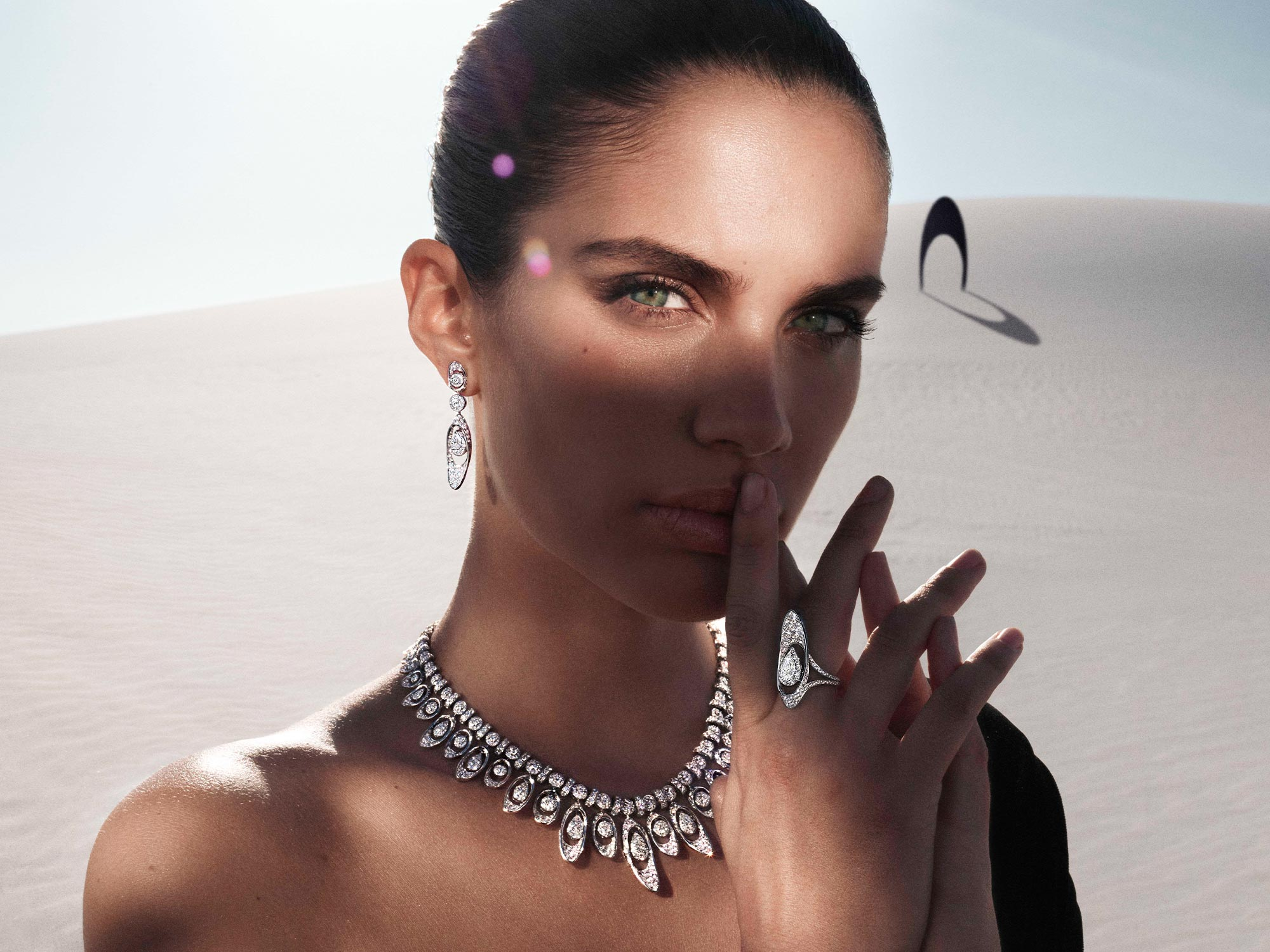 Close up of a model wearing Graff Gateway diamond earrings, necklace and ring from the Tribal jewellery collection, in a desert