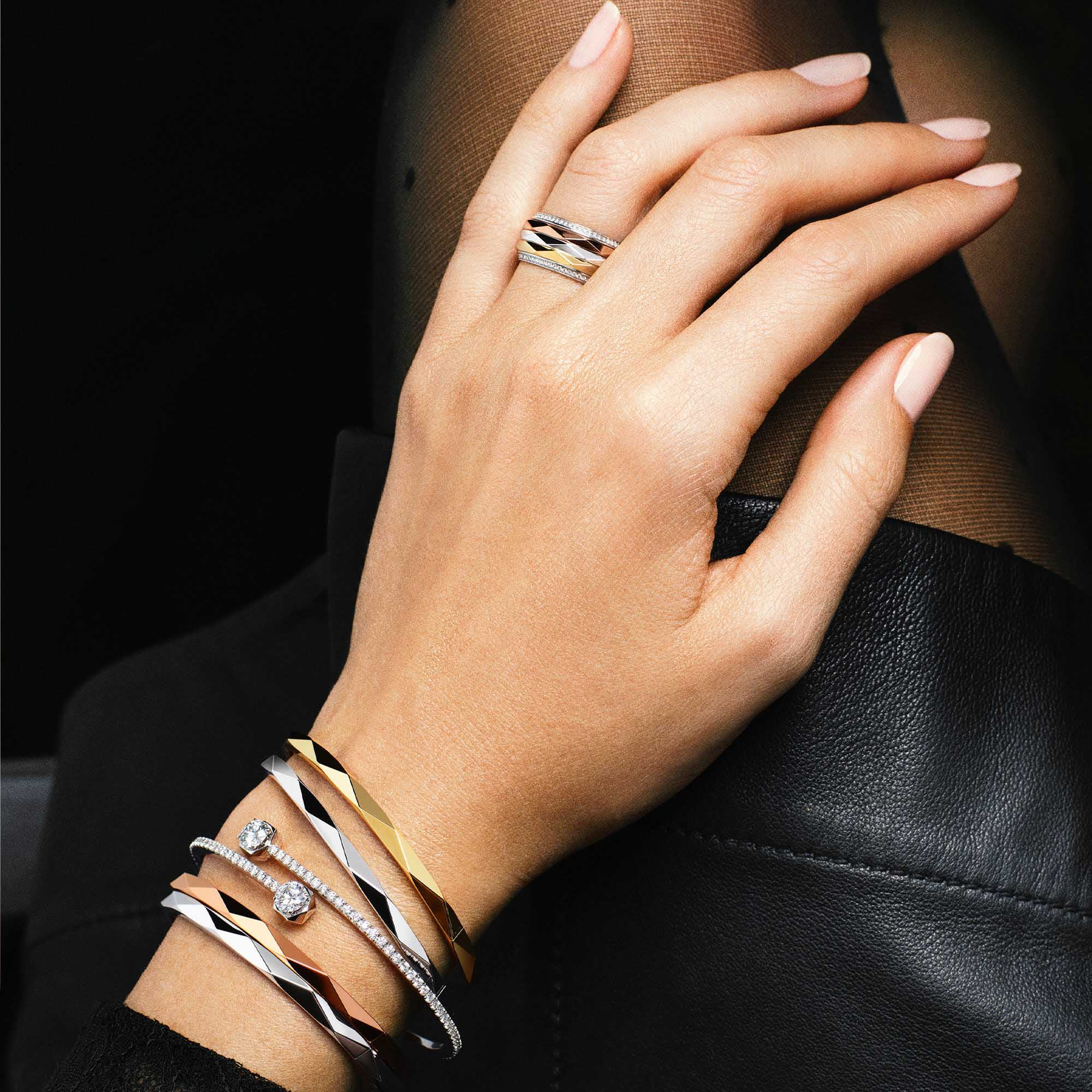 Close up of a model's hand wearing Graff Laurence Graff Signature jewellery collection rings and bracelets
