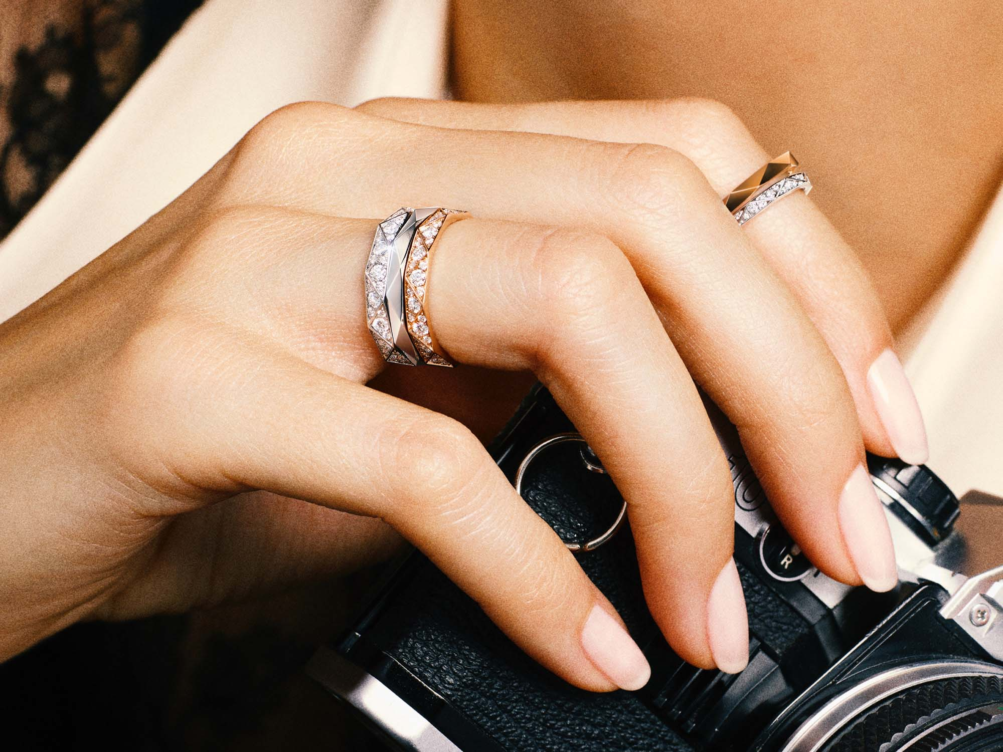 Model holding camera and wearing Laurence Graff signature bands, white gold and rose gold pave and rose gold plain.