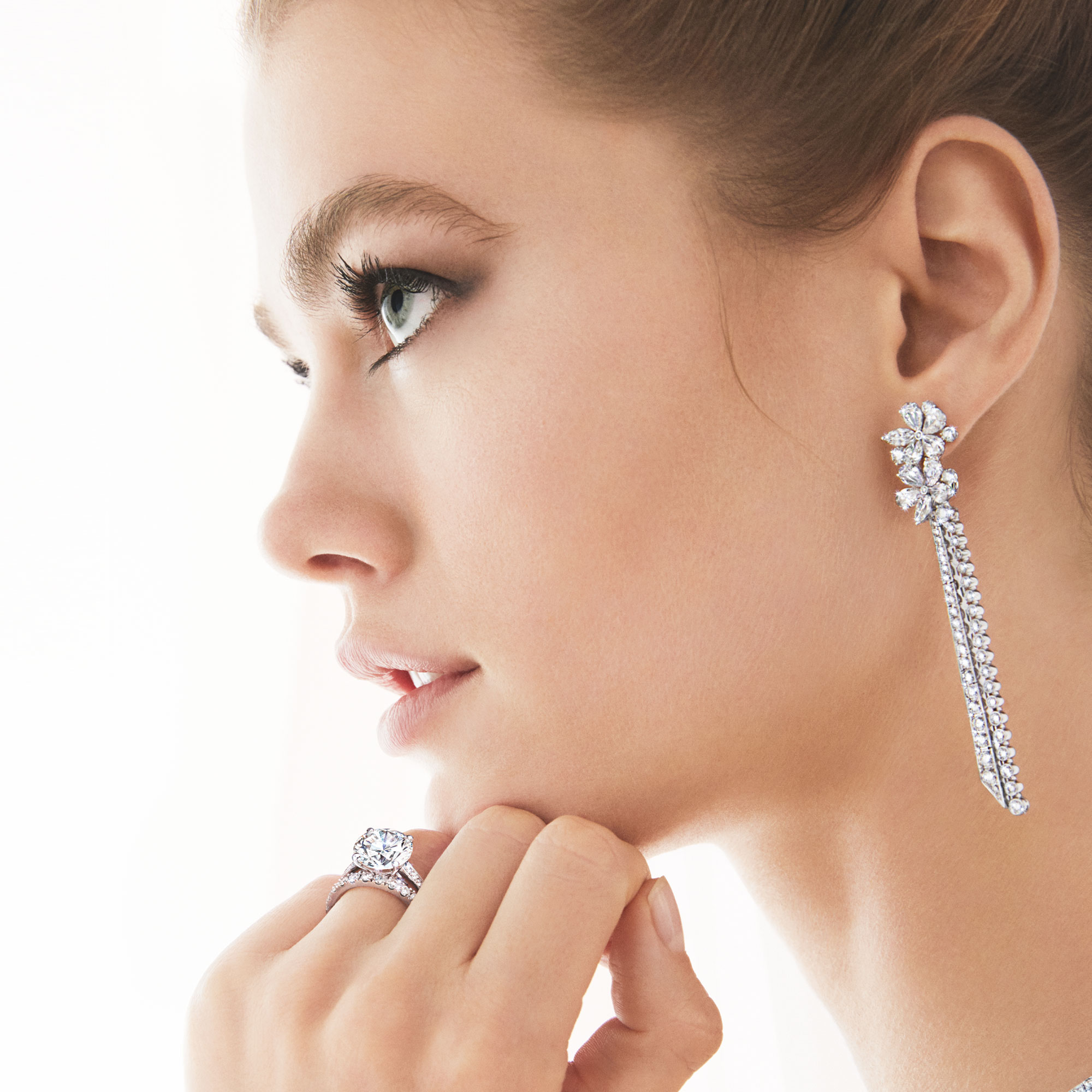 Model wears Graff Carissa Diamond Drop Earrings, round Diamond Solitaire and Castle Set Round Diamond Wedding Band.