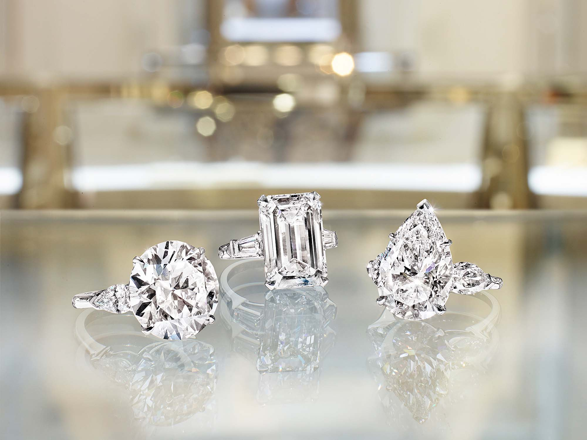 Three Graff Promise Engagement rings set with round diamond, pear Shape Diamond and Emerald Cut Diamond.