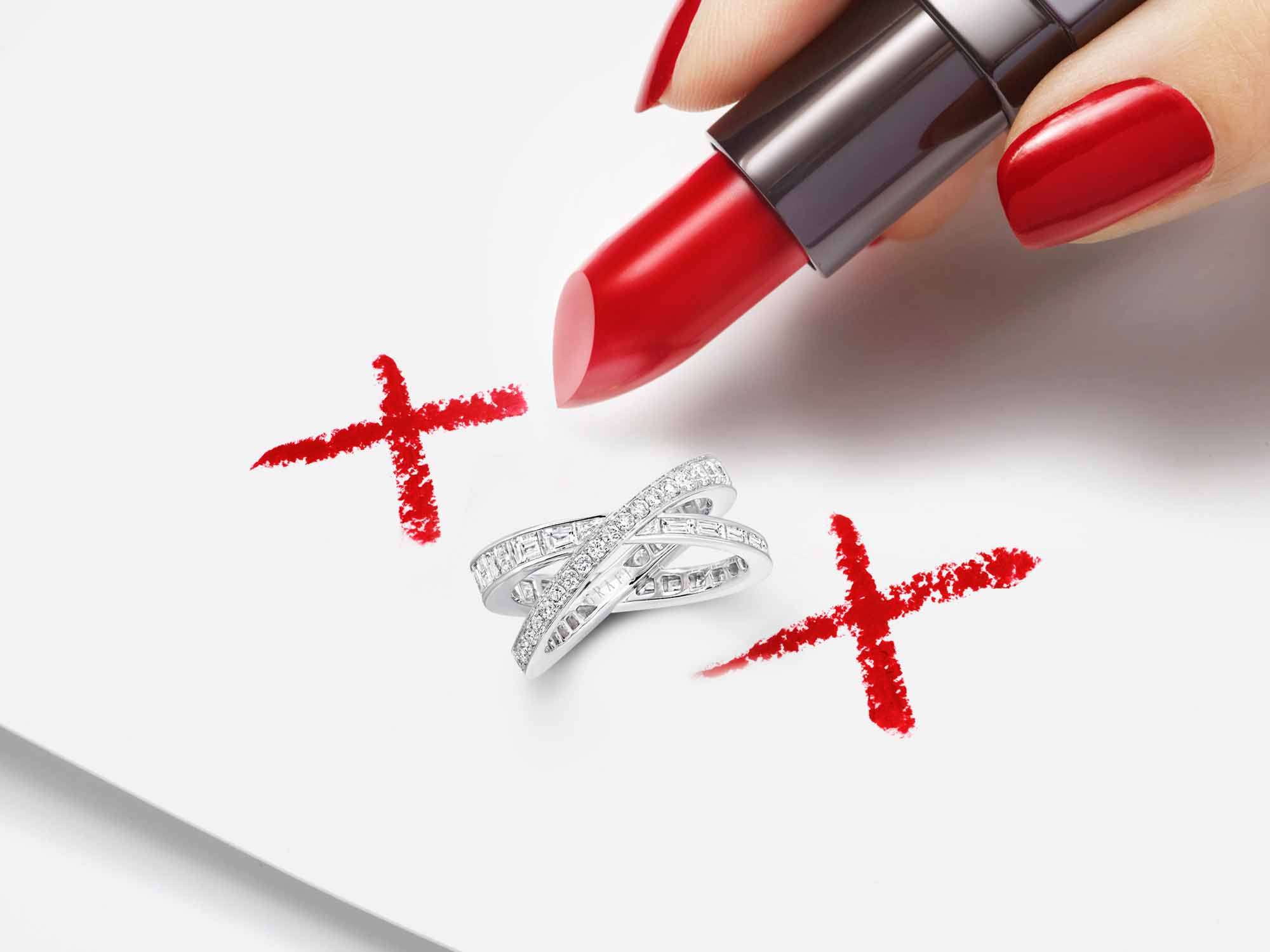 Model drawing kiss symbols with red lipstick and a Kiss Pavé Baguette and round Diamond Ring  from the Graff Spiral Jewellery Collection in the middle