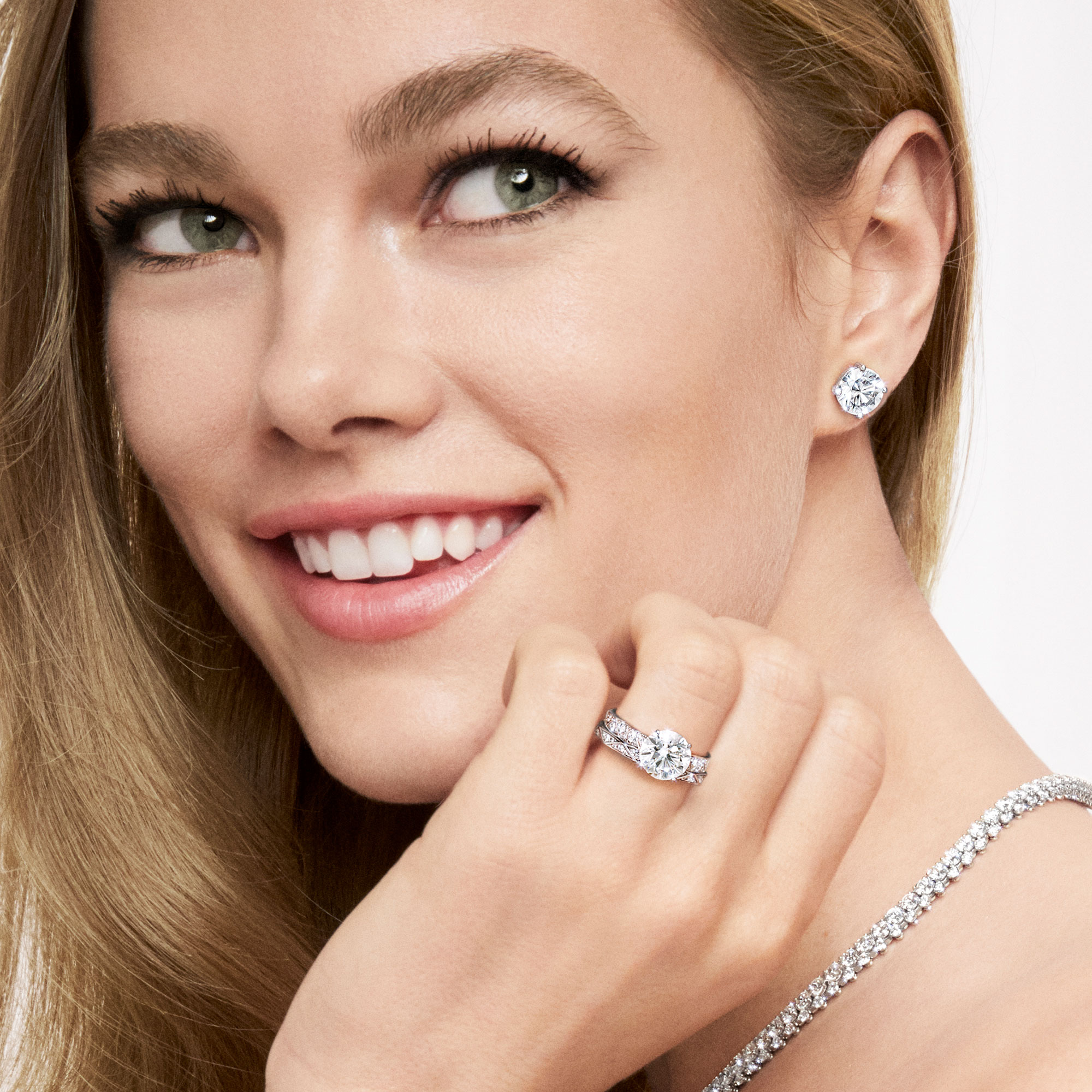 Model wearing Graff Round Diamond Stud Earrings and Laurence Graff Signature Round Diamond Engagement Ring and wessing band.